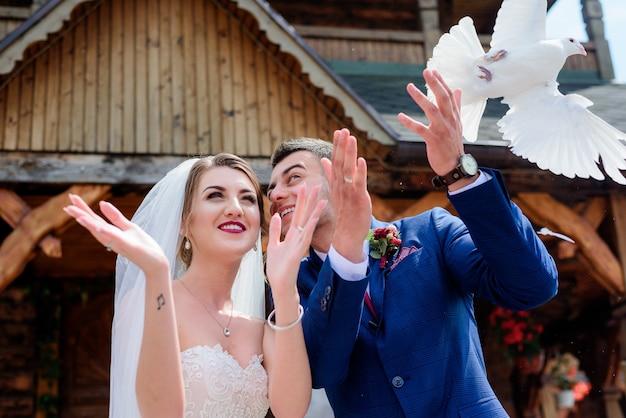 La sposa e lo sposo tengono i piccioni in piedi davanti a una chiesa di legno