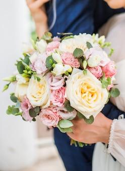 Sposa e sposo che tengono il bellissimo mazzo di fiori da sposa.