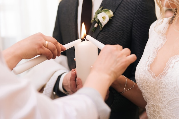 Sposa e sposo che tengono una candela. tradizione di accensione del focolare familiare