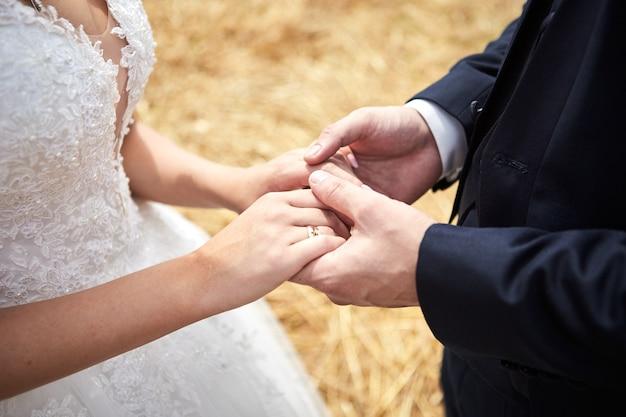 Sposa e sposo che tengono le mani all'aperto