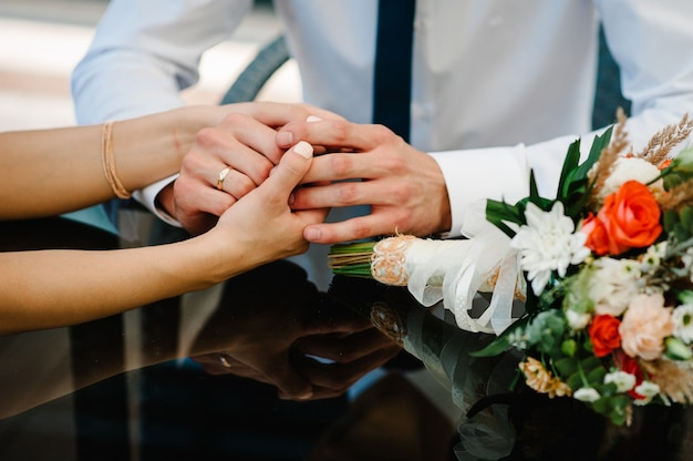 La sposa e lo sposo si tengono per mano con il suo bouquet
