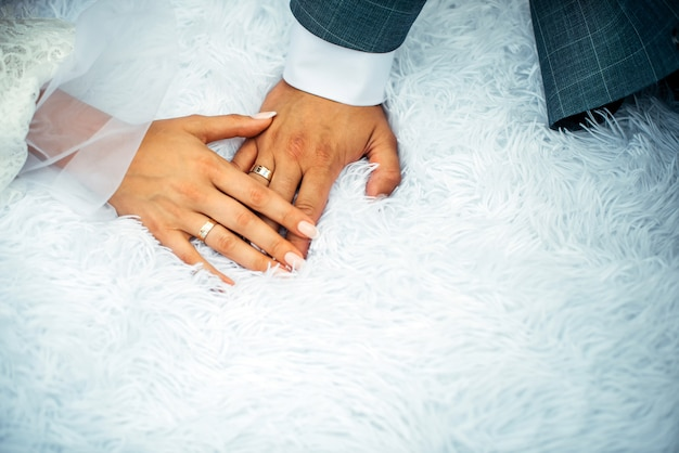 Sposa e sposo che si tengono per mano con la mano della donna sulla mano dell'uomo con le fedi nuziali