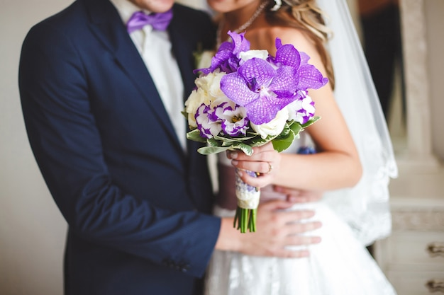 La sposa e lo sposo in possesso di un bouquet da sposa di fiori