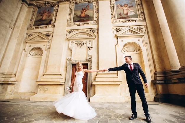 La sposa e lo sposo si abbracciano, si baciano all'aperto il giorno del matrimonio, la giovane coppia cammina a praga, il giorno di san valentino