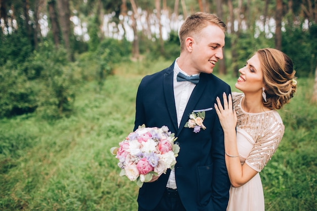 Sposa e sposo che abbracciano il giorno del matrimonio, giovani coppie felici che baciano nel parco in natura, san valentino