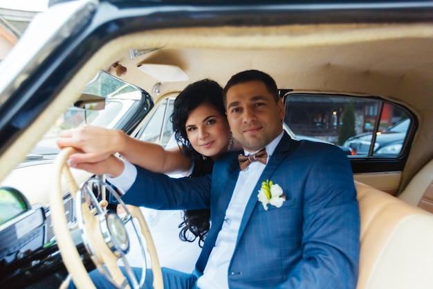 Sposa e sposo all'interno di un'auto classica. loro sono felici.