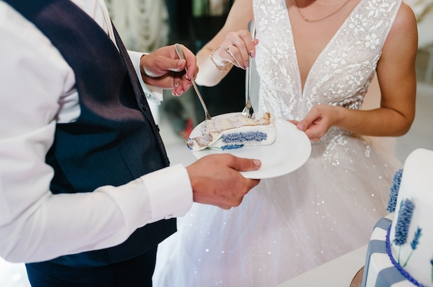 La sposa e lo sposo stanno mangiando una torta nuziale rustica con delicati fiori viola.