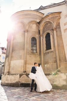 Sposa e sposo che si baciano vicino agli edifici della chiesa della chiesa con una bellissima architettura