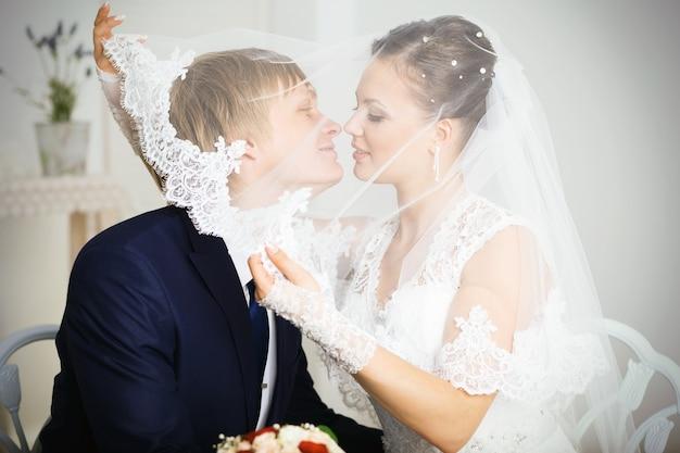 Sposa e sposo che si baciano sotto il velo che tiene il mazzo di fiori in mano.