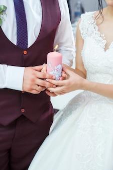 La sposa e lo sposo accendono una candela insieme il giorno del matrimonio