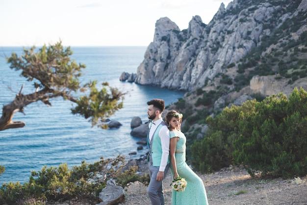 La sposa e lo sposo sulla natura in montagna vicino all'acqua. abito e vestito colore tiffany. schiena contro schiena.
