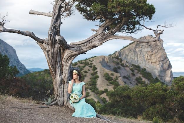 La sposa e lo sposo sulla natura in montagna vicino all'acqua. abito e abito color tiffany. la sposa siede sotto un albero.