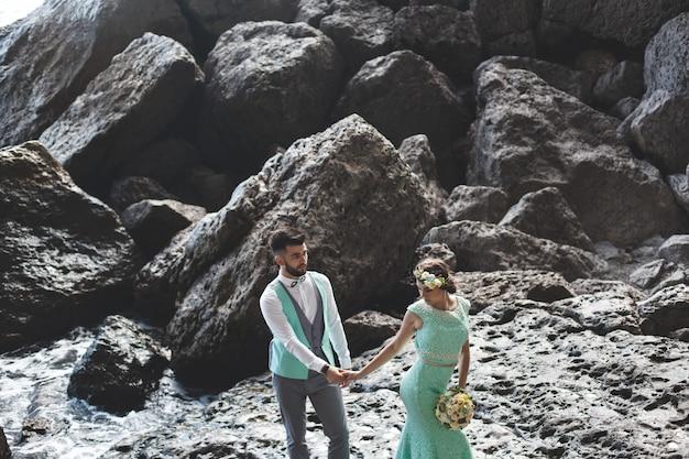 La sposa e lo sposo sulla natura in montagna vicino all'acqua. abito e abito color tiffany. danza.