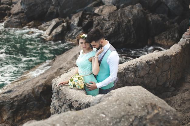 La sposa e lo sposo sulla natura in montagna vicino all'acqua. abito e abito color tiffany. baci e abbracci.