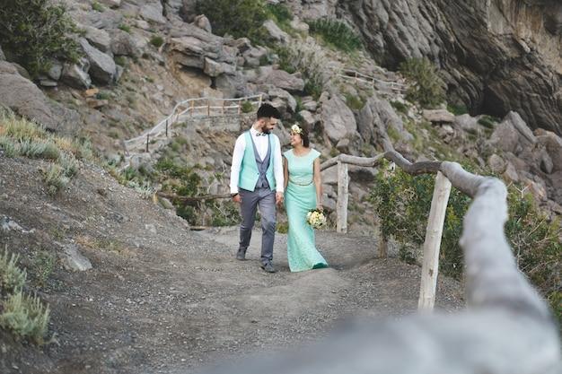 La sposa e lo sposo sulla natura in montagna vicino all'acqua. abito e abito color tiffany. cammina mano nella mano.
