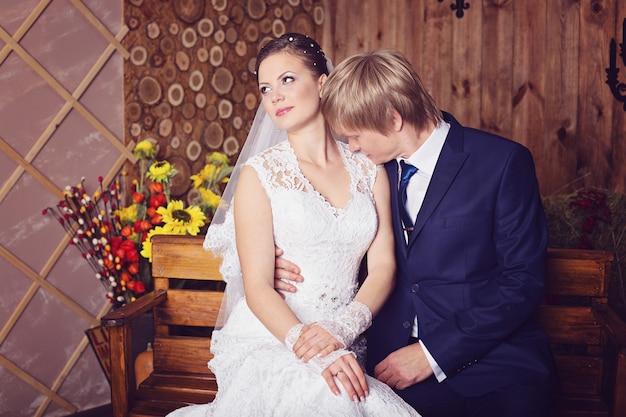 Sposa e sposo seduti su una panchina in studio con interni d'epoca