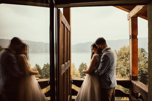 Gli sposi si alzano e si abbracciano sul balcone e guardano il bellissimo paesaggio.
