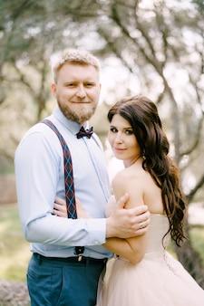 Gli sposi stanno abbracciati tra gli alberi dell'uliveto