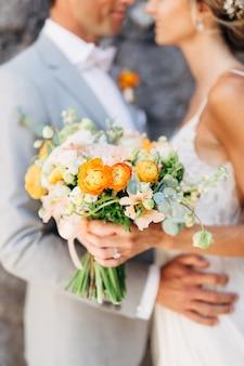 Gli sposi stanno abbracciando un muro di mattoni nella città vecchia e tengono in mano un bouquet da sposa