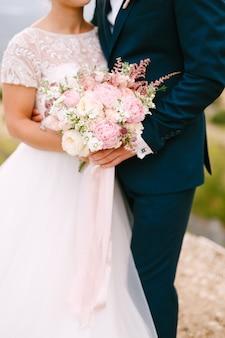 Gli sposi stanno abbracciando e reggono il bouquet della sposa con delicate peonie di rose rosa