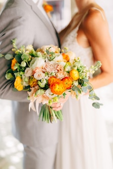 Gli sposi stanno abbracciando e tengono in mano un bouquet da sposa con ranuncoli arancioni e rose