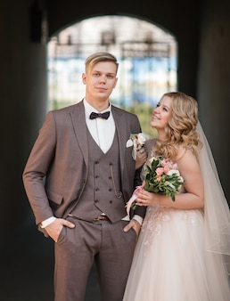 Sposa e sposo in piedi sotto l'arco dell'edificio della città. feste ed eventi