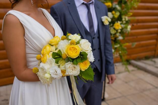 Sposa e sposo in piedi sull'erba verde e con in mano un mazzo di fiori bianchi e gialli con il verde