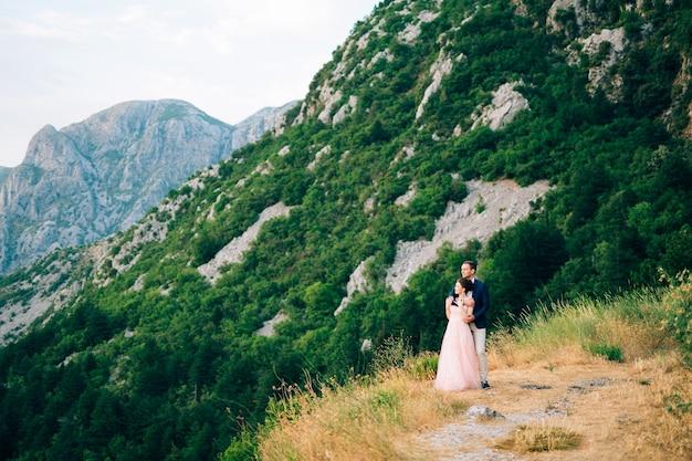 Sposa e sposo in piedi sulla montagna: lo sposo abbraccia dolcemente la sposa da dietro.