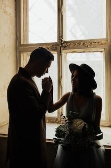 La sposa e lo sposo in piedi davanti alla finestra si tengono per mano, guardandosi.