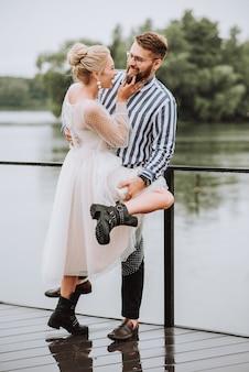 Gli sposi che si abbracciano teneramente stanno in piedi e posano sul molo.