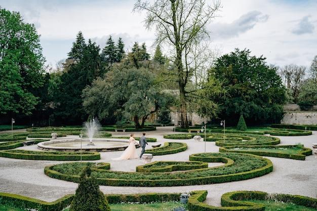 La sposa e lo sposo camminano mano nella mano in un bellissimo parco in italia