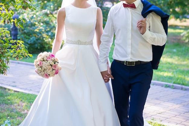 La sposa e lo sposo camminano e si tengono per mano con un bouquet da sposa da vicino in una giornata estiva