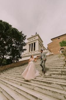 Sposa e sposo che camminano all'aperto a piazza spagna e trinità dei monti a roma, italia