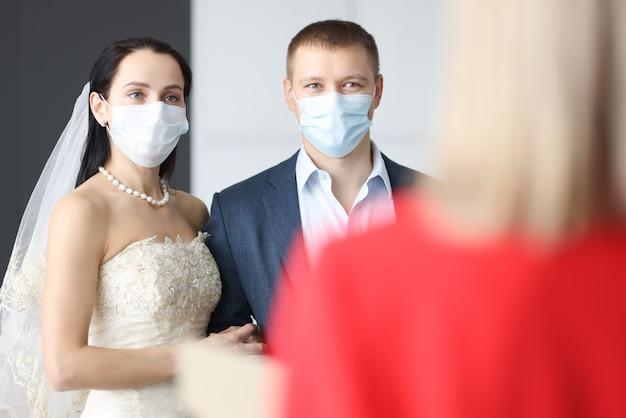 Sposa e sposo che indossano maschere protettive mediche in piedi davanti alla receptionist