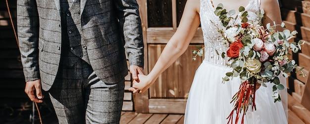 La sposa e lo sposo il giorno del matrimonio si abbracciano e mostrano amore con un bouquet da sposa di fiori di rosa
