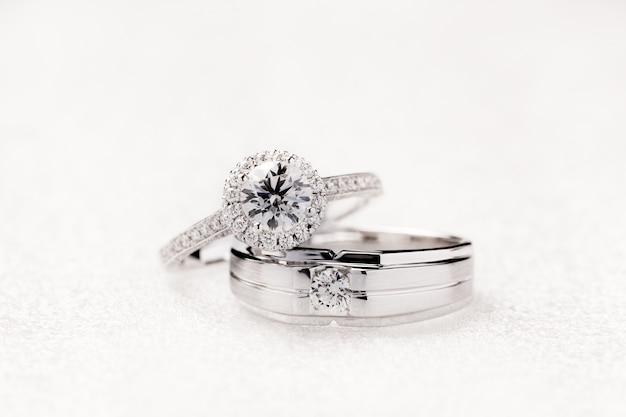 Anelli di fidanzamento di nozze dello sposo e della sposa su fondo bianco
