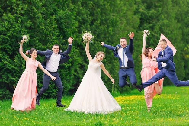 La sposa e lo sposo con testimoni dello sposo e damigelle d'onore felici saltano, divertendosi nel parco.