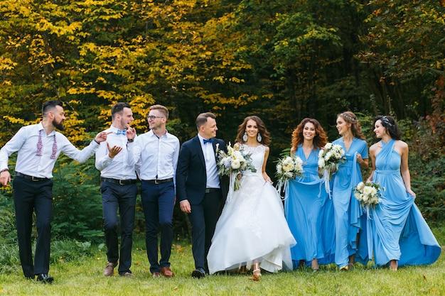 La sposa e lo sposo con i testimoni dello sposo felici e le damigelle stanno vicino alla vecchia auto retrò bianca.