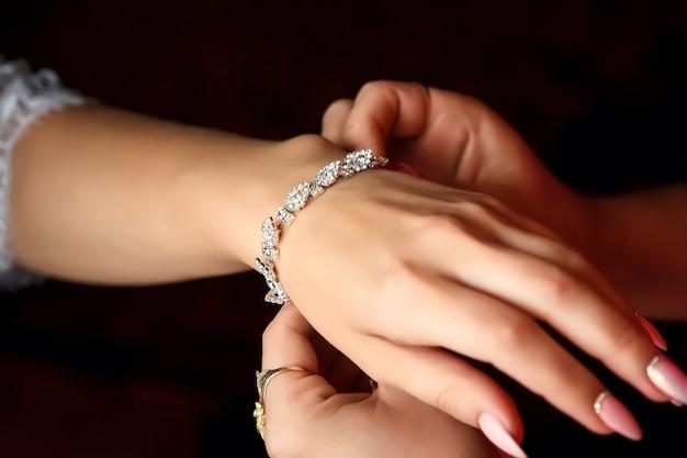 La sposa passa la bella decorazione sul braccio, braccialetto.