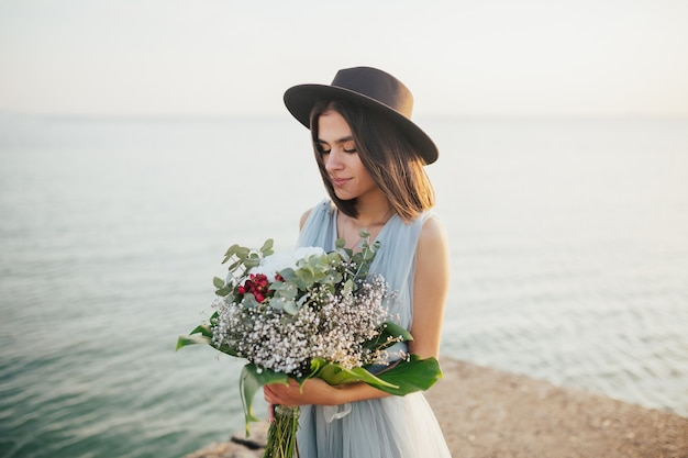 Sposa in cappello e abito da sposa blu che tiene il mazzo di fiori