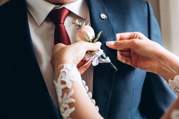 Sposa che aiuta lo sposo a prepararsi per il matrimonio