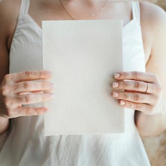 Sposa con in mano un biglietto bianco vuoto
