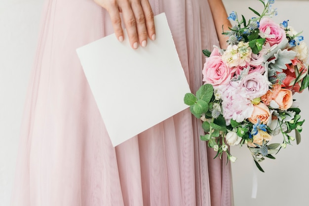 Sposa con in mano un biglietto con un mazzo di fiori