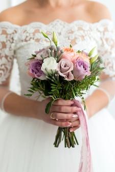 La sposa tiene in mano un bouquet di bellissimi fiori delicati