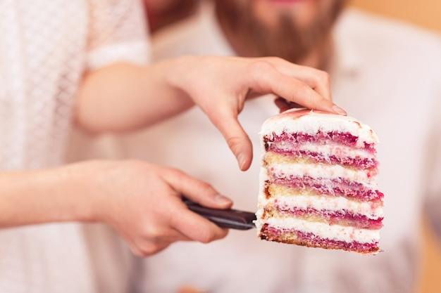 La sposa tiene un pezzo di torta nuziale nelle sue mani e dà lo sposo.
