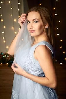 La sposa tiene un velo tra le mani su uno sfondo scuro con ghirlande