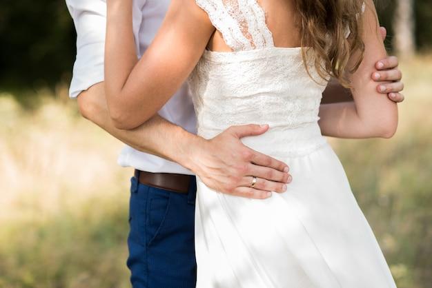 La sposa abbraccia lo sposo e tiene in mano un bouquet da sposa con fiori blu sullo sfondo della foresta