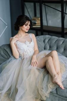 La sposa è una bruna dall'aspetto europeo. singolo ritratto. trucco e acconciatura da sposa. modello. mattina della sposa. boudoir in hotel.