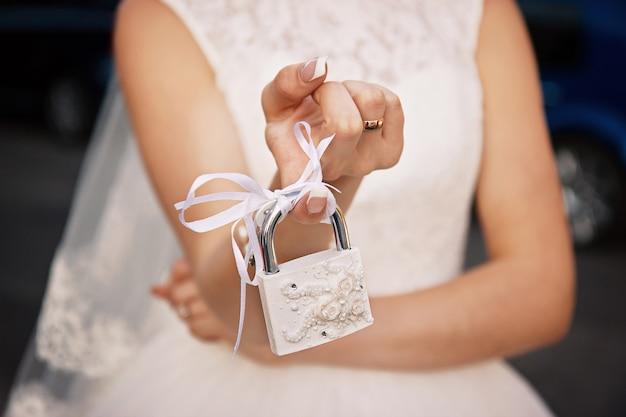 La sposa tiene in mano un lucchetto chiuso bianco