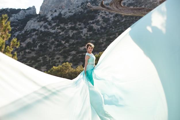 Sposa in natura in montagna vicino all'acqua. colore del vestito tiffany. la sposa sta giocando con il suo vestito.